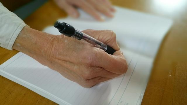 老人が書類にサイン